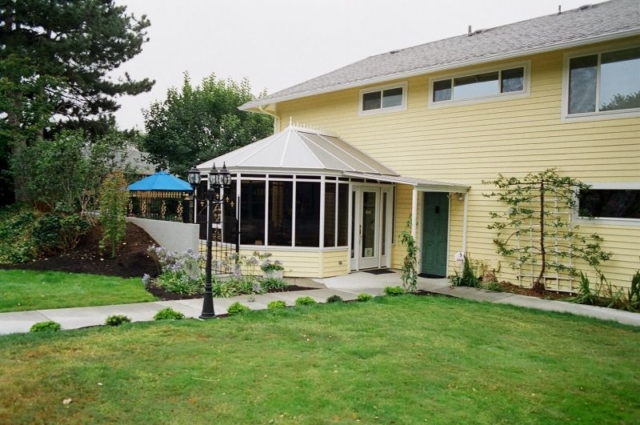 Yellow conservatory with dark windows attached to a home