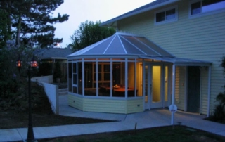 Night view of a yellow conservatory with dark windows attached to a home