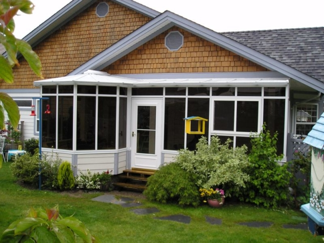 White combined-style conservatory with dark windows