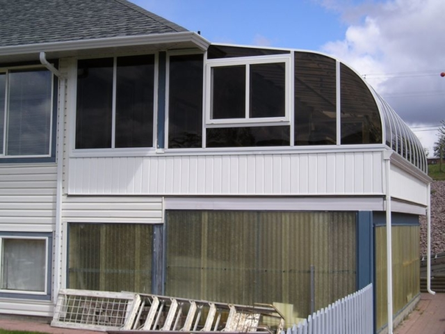 Exterior view of a curved eave sunroom on the second floor of a house