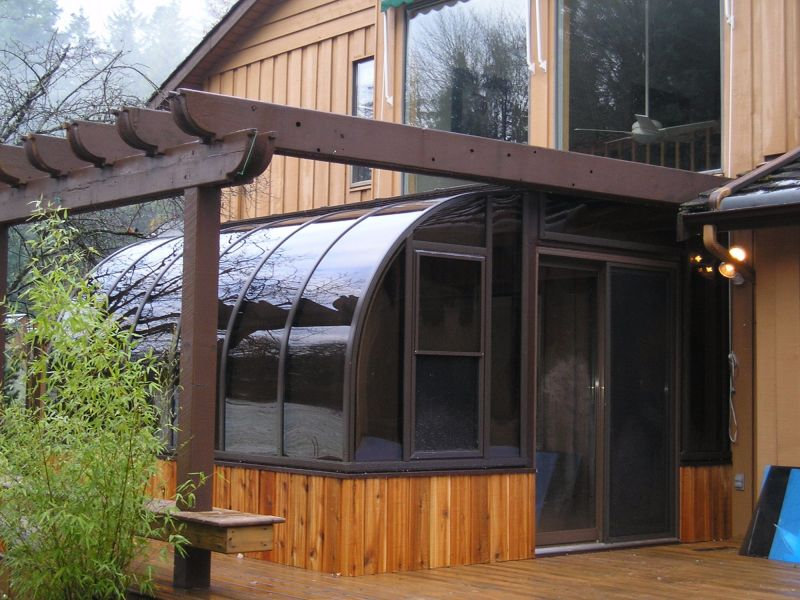 Exterior view of a brown sunroom with wood trim