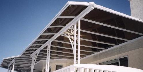 Black and white curved end patio cover that extends around the corner of a building