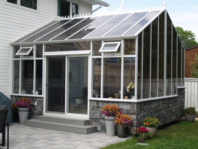 An exterior view of a gable-style conservatory attached to a home