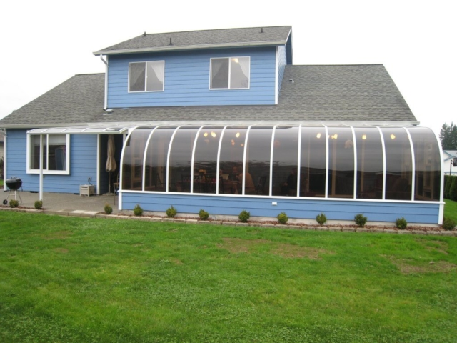 Exterior view of a large curved eave sunroom with an attached patio cover