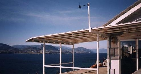 A patio cover with a white frame covering a deck with a lakeside overlook