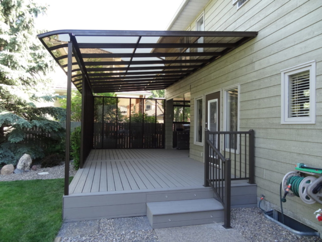 A curved end patio cover with a dark frame and transparent windows