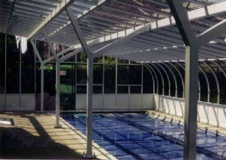 A large sunroom enclosing a swimming pool