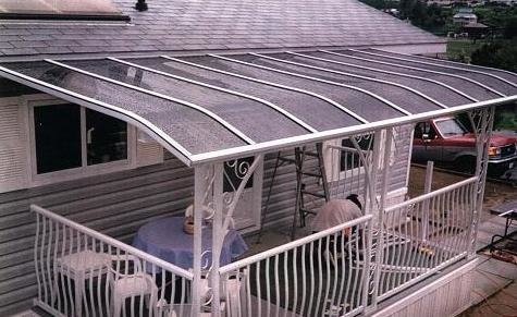 A white patio cover over a small deck with a white railing