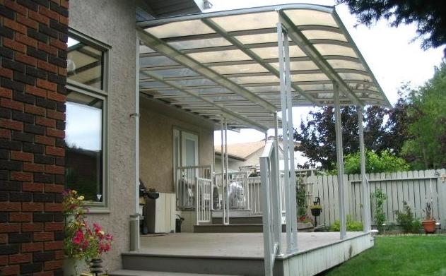 A white curved end patio cover of a small deck with steps