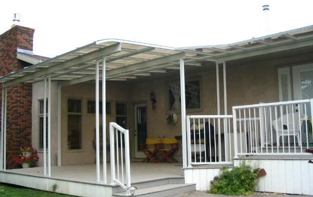 A white and transparent patio cover covering a deck with varying lengths