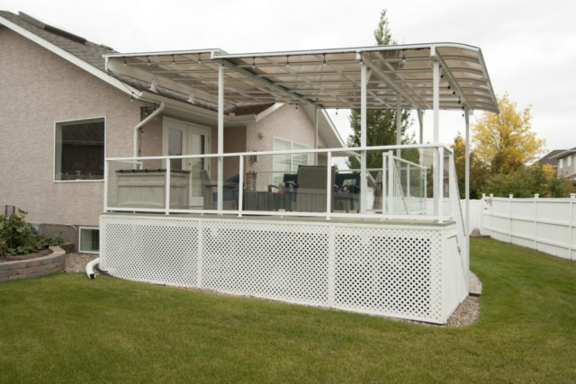 A white patio cover with lights covering a raised deck with stairs