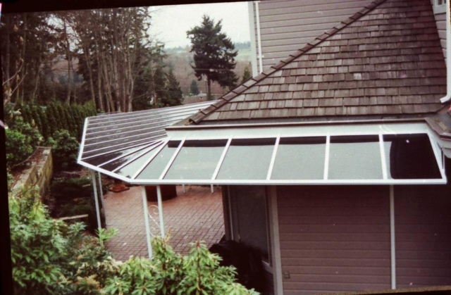 A straight end patio cover with a white frame that extends around a building