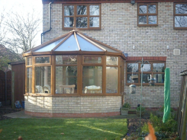 Exterior view of a Victorian-style brown and brick conservatory attached to a home