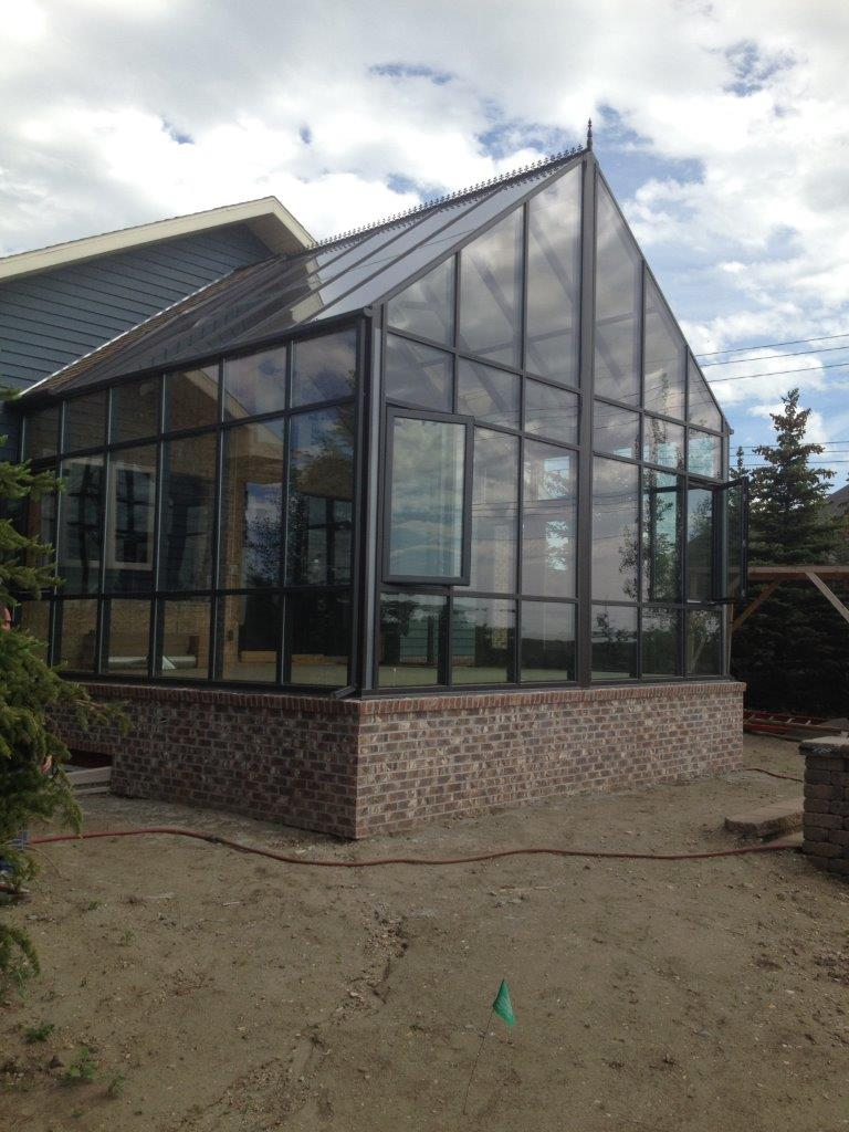Exterior view of a new brown gable-style conservatory with a brick foundation
