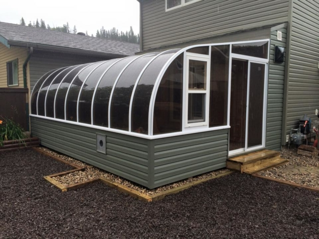 Exterior view of a curved eave sunroom with siding to match the house