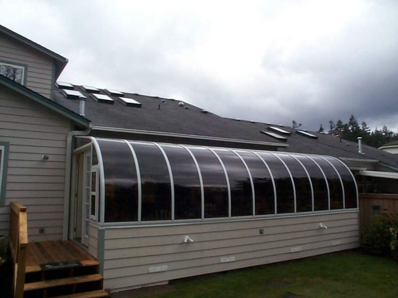 Exterior view of a curved eave sunroom attached to a house