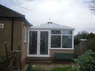Small white and brick Edwardian-style conservatory attached to a home