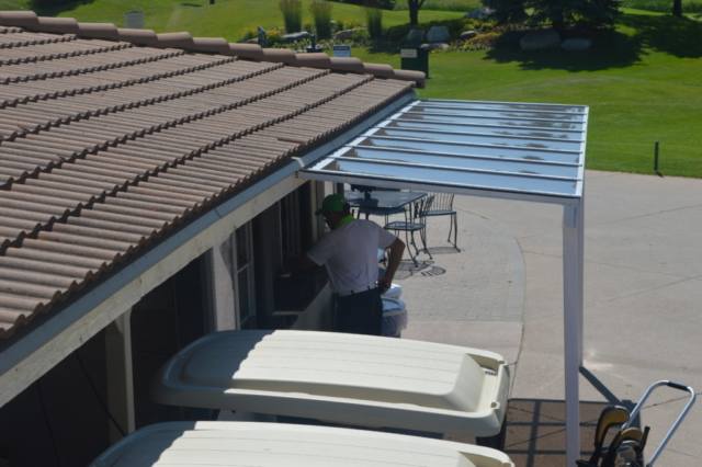 An alternate view of a small patio cover used to shade a lunch counter at a golf course