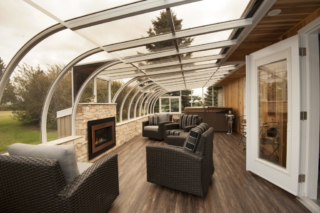 Interior view of a large curved eave sunroom with fireplace and furniture