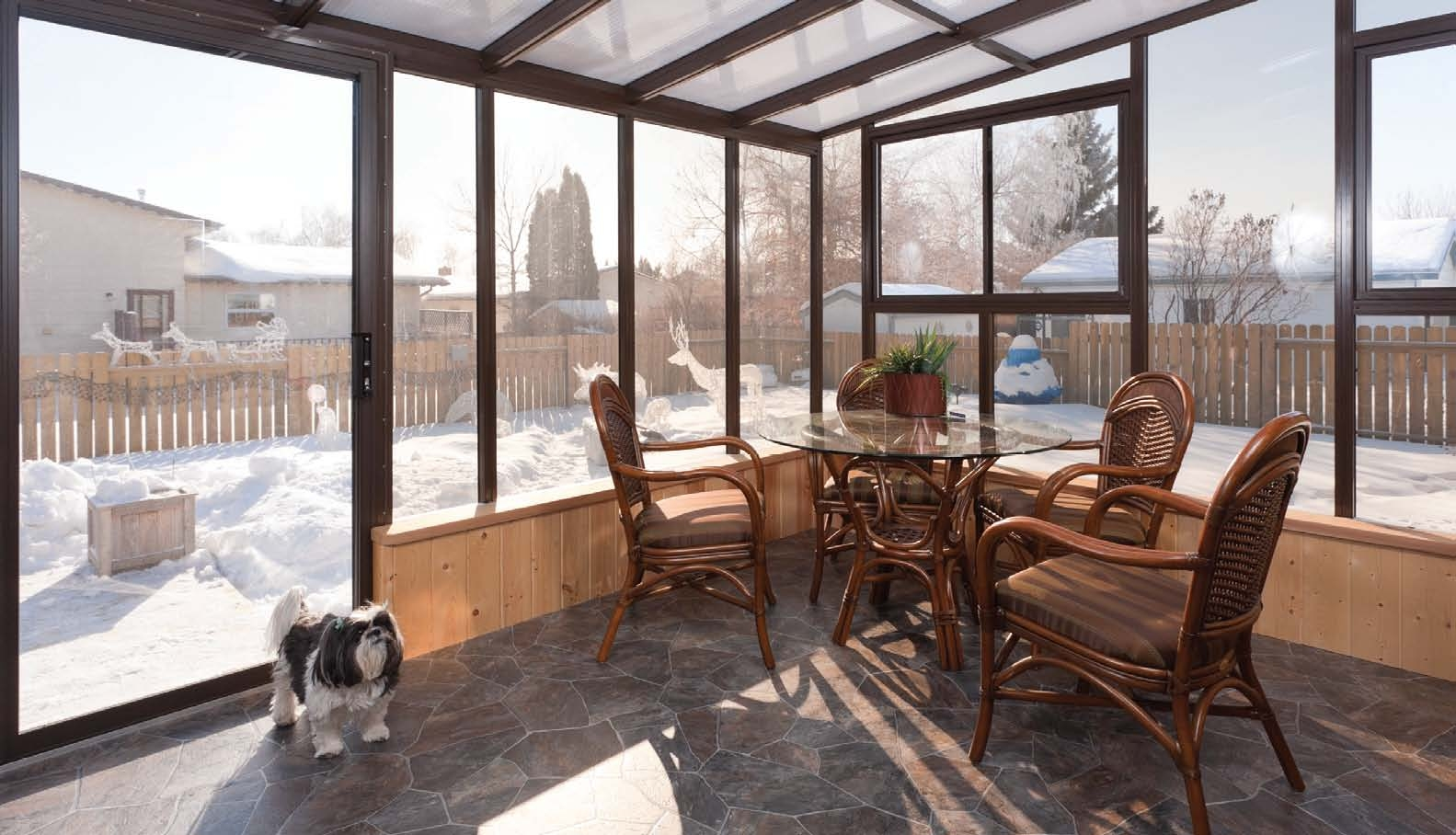 Decorated interior view of a sunroom including table, chairs, and dog