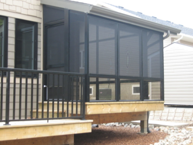An exterior view of a screen room that connects to a deck