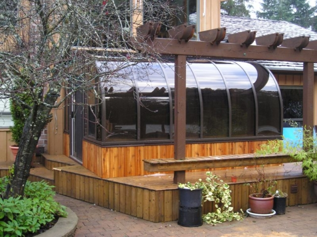 Exterior view of a small dark brown sunroom with wood trim