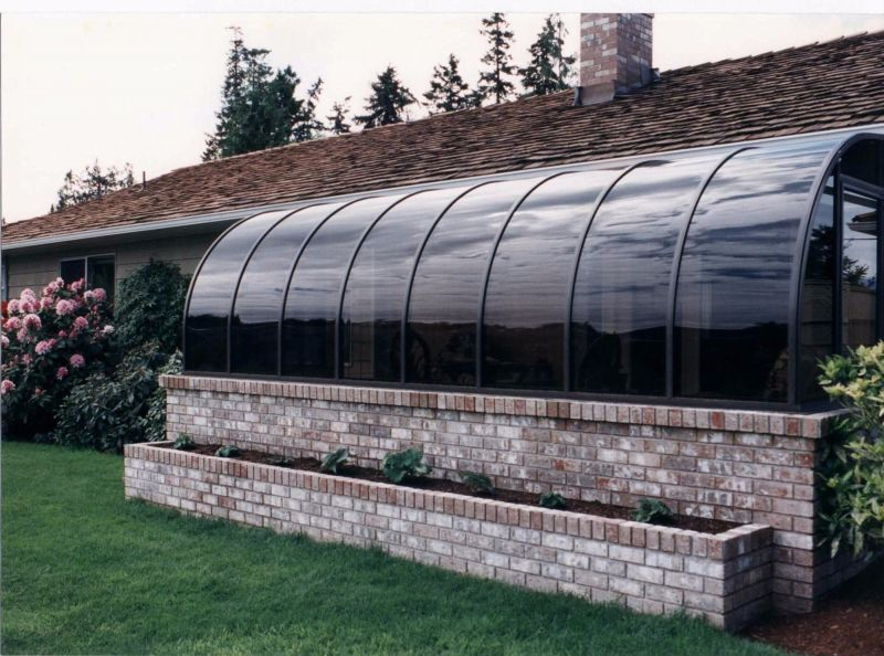 Exterior view of a sunroom with brick trim