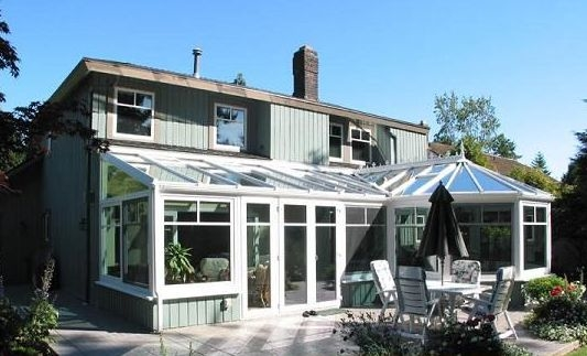 Exterior view of a white combined-style conservatory attached to a house