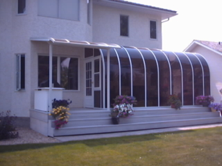 Exterior view of a white curved eave sunroom with dark windows