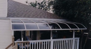 A curved end patio cover with a white frame covering a small deck