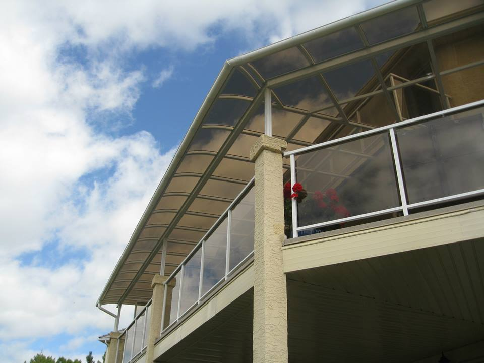 A white patio cover on a second-floor deck that extends around a corner