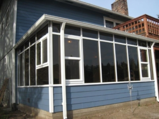 A small straight eave sunroom with dark windows