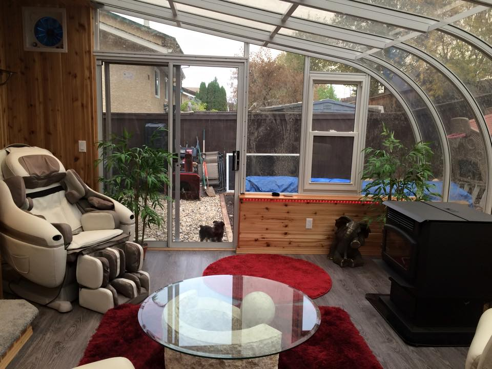 Alternate view of a well-decorated interior of a white sunroom with clear windows