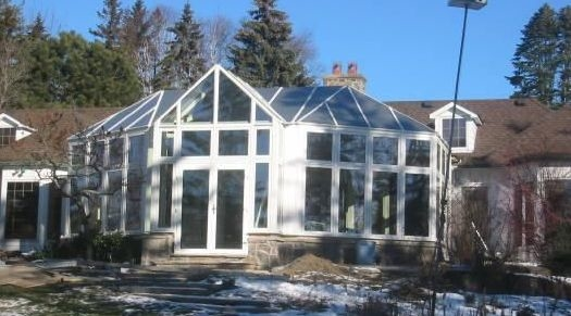 Exterior view of a white Victorian conservatory with a stone foundation