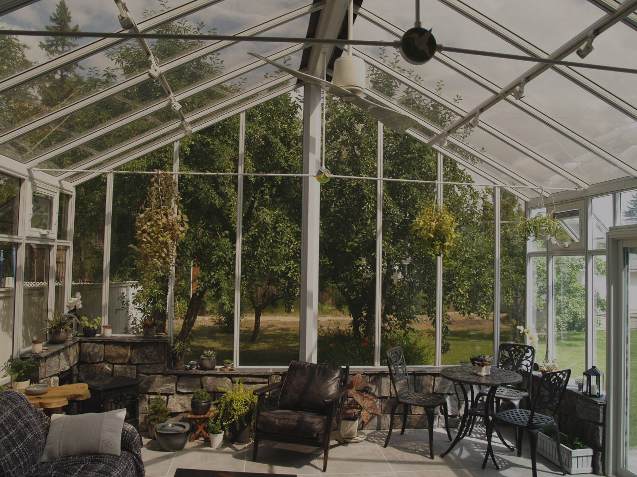 An interior view of a large white gable-style conservatory with clear windows and furniture