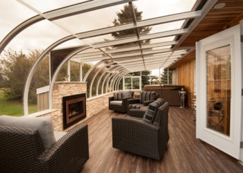 A white curved eave sunroom with furniture and fireplace