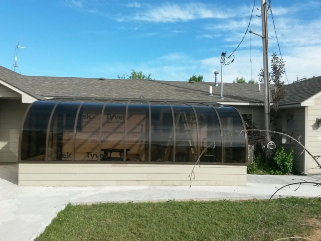 Exterior of house with brown curved sunroom Montana
