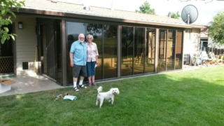 Two people outside of a brown solarium attached to back of house with white dog